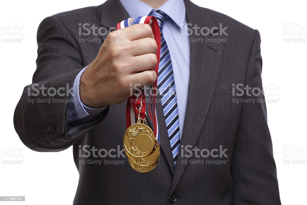 A man in a business suit holding gold medals stock photo