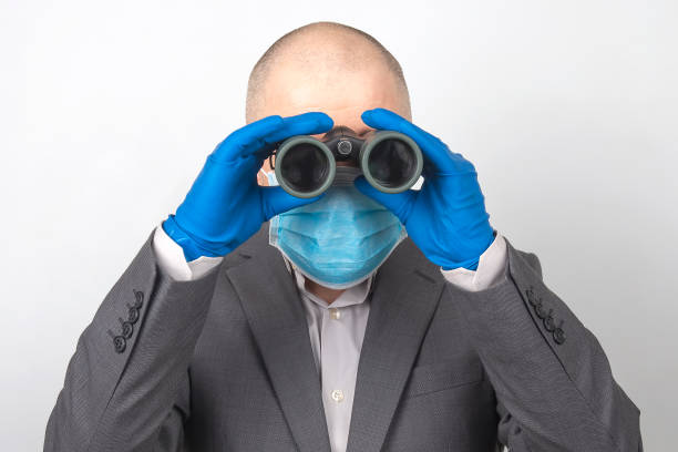 man in a business suit in a medical mask and protective gloves looks through binoculars. goals in a successful business with quarantine problems in the coronavirus epidemic. stock photo