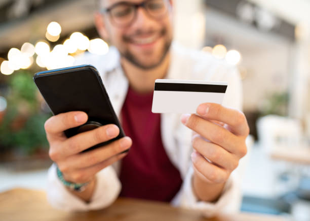 A man in a cafe with a smatphone and a credit card, shopping online.A man in a cafe holding a smatphone and a credit card, shopping online. Selective focus on the hands, the phone, and the credit card. stock photo