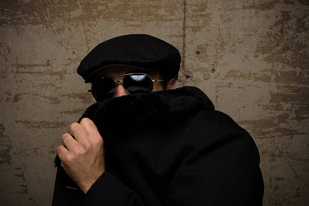 A man in a cap and dark glasses hides his face with his coat stock photo