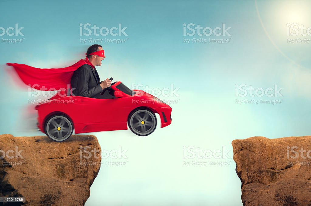 man in a car jumping a ravine stock photo