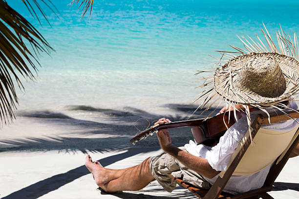 man in a chair playing guitar at the Caribbean beach stock photo