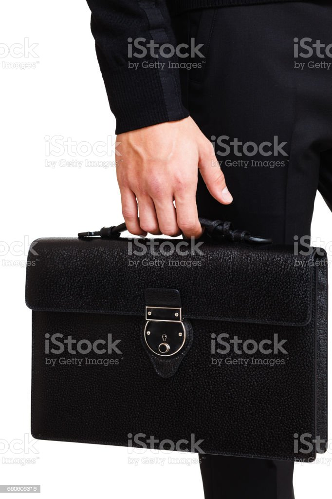 A man in a classic suit holds a black briefcase royalty-free stock photo