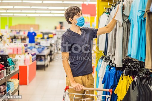 istock Man in a clothing store in a medical mask because of a coronovirus. Quarantine is over, now you can go to the clothing store 1220917459