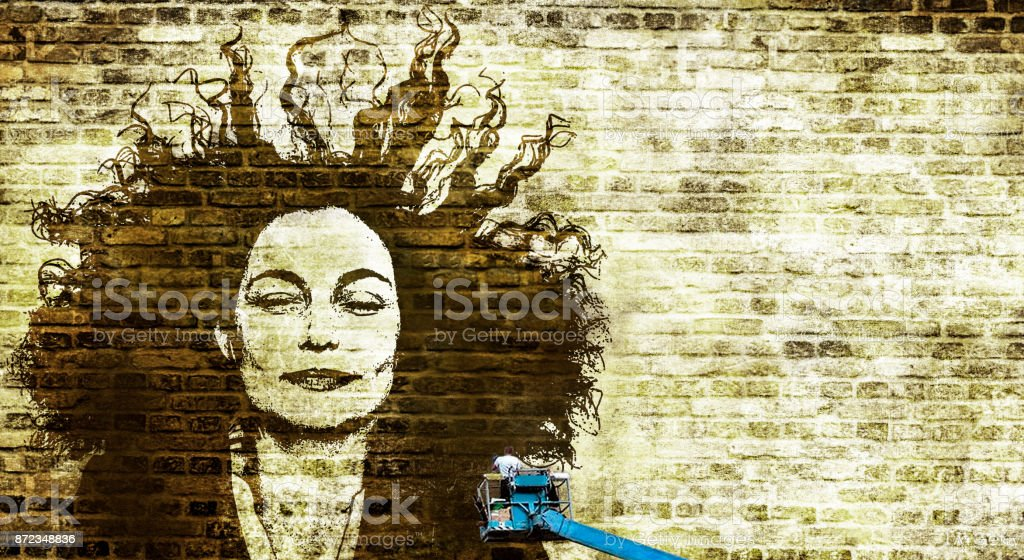 A man in a crane painting beautiful womans face on a wall stock photo