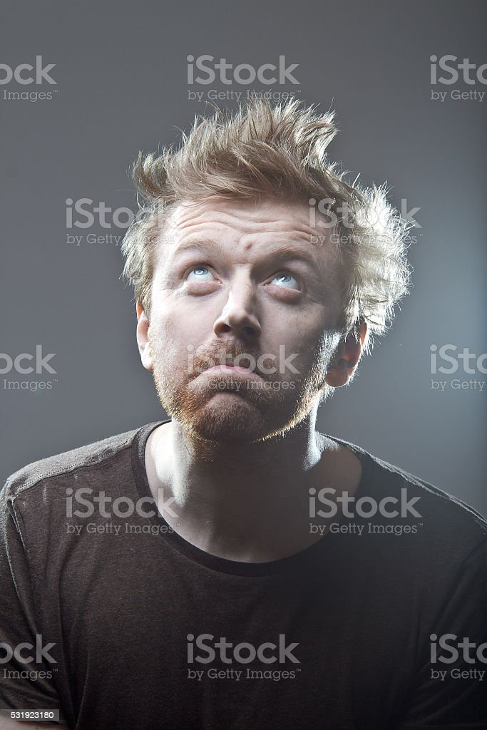 Man in a dark brown t-shirt with flare looking up stock photo