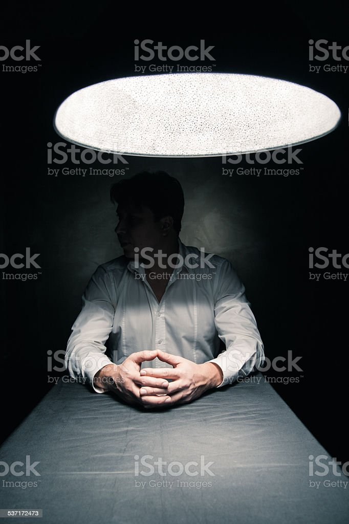 Man in a dark room illuminated only by lamp stock photo