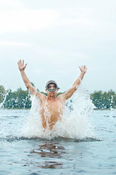 mann mit einem taucher maske springt aus dem wasser produzieren eine menge spray - pop up stock-fotos und bilder