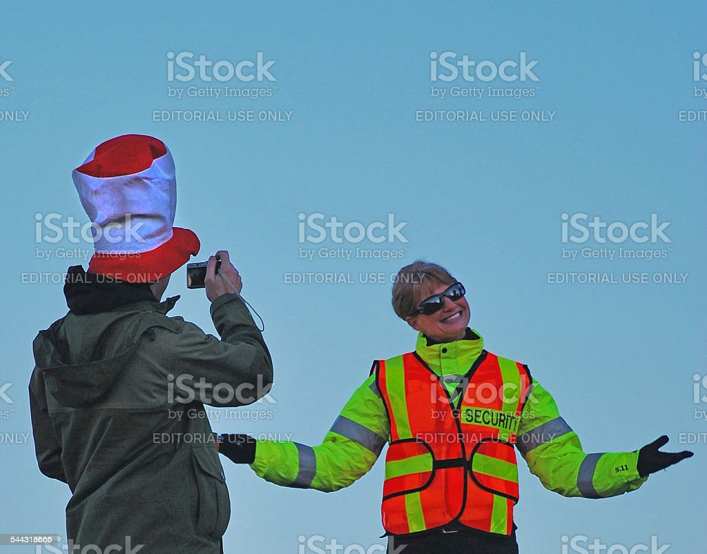 Man in a Dr. Seuss hat photographing female security guard stock photo