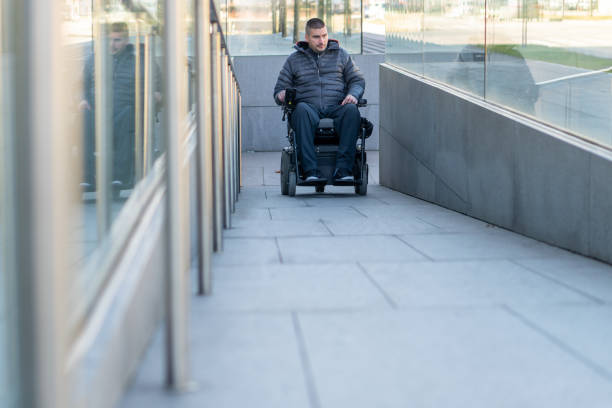 Man in a electric wheelchair using a ramp stock photo
