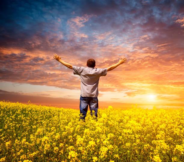 Mann auf einem Feld mit Vergewaltigung mit erhobenen Armen in den Himmel – Foto