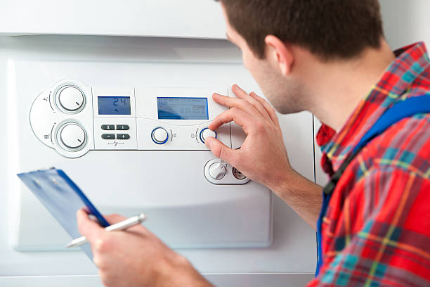 A man in a flannel shirt works on a gas boiler stock photo