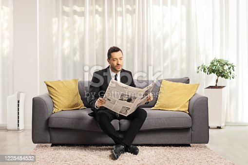 Full length portrait of a man in a formal suit sitting on a sofa and reading a newspaper in a living room