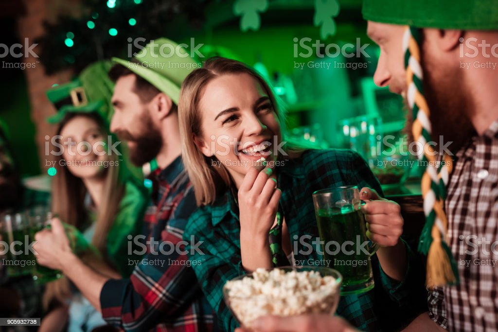 A man in a funny hat and a girl are drinking beer together and eating popcorn. stock photo