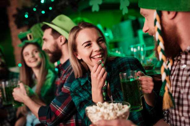 a man in a funny hat and a girl are drinking beer together and eating popcorn. - st patricks day food stock photos and pictures