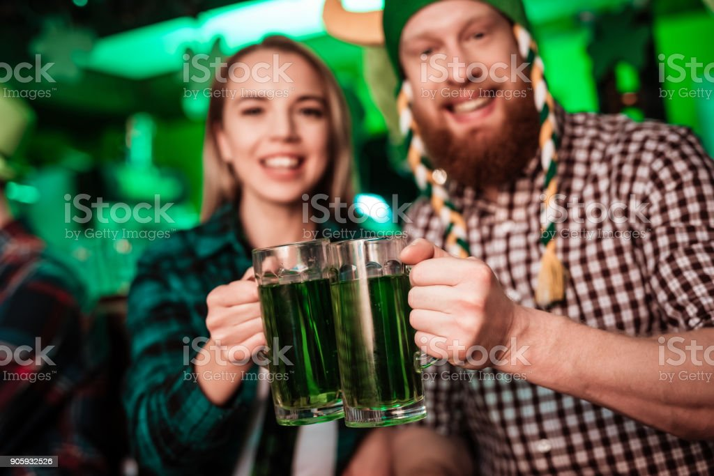 A man in a funny hat and a girl are drinking beer together. stock photo