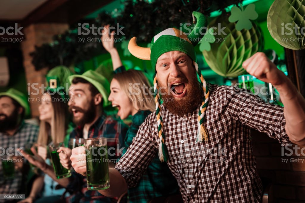 A man in a funny hat celebrates St. Patrick's Day with friends. stock photo