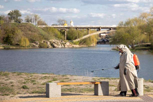 Ein Mann im grauen Mantel behandelt den Bereich mit einer Reinigungslösung. Geschäfte, Mülltonnen Verarbeitung von Covid-19. Die Covid-19-Epidemie. Pandemie. Strand. Fluss. – Foto