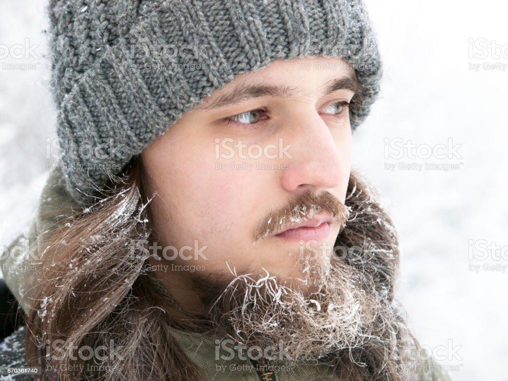 Um homem com um chapéu de malha cinzento, com fosco barba e cabelo comprido no inverno. - foto de acervo