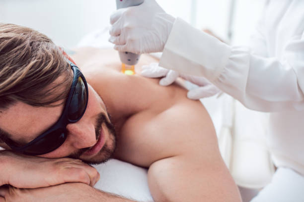 Man in a hair removal studio stock photo
