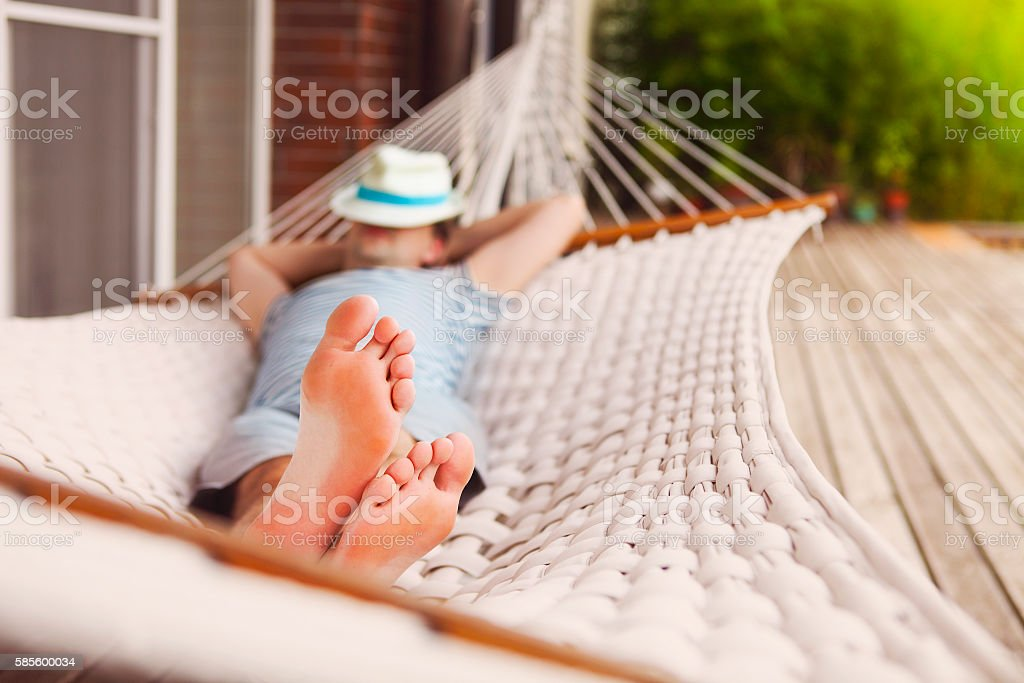 Man in a hammock on summer day - foto de acervo