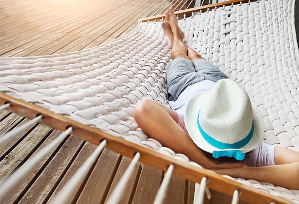 Man in a hammock on summer day stock photo