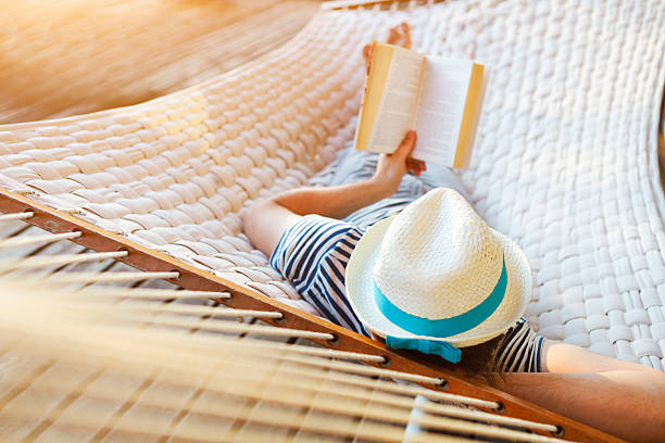man in a hammock with book on summer day - hangmat stockfoto's en -beelden