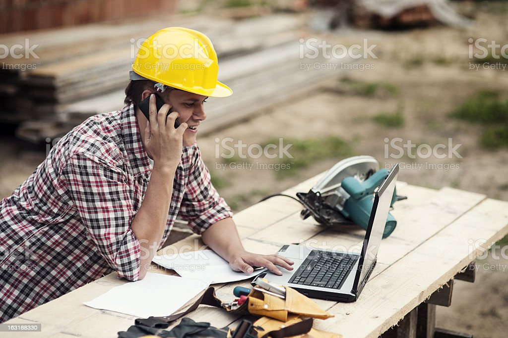 Man in a hard hat at an outdoor worksite on phone and laptop stock photo