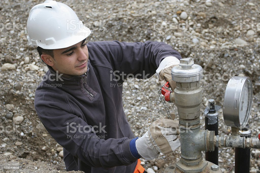 A man in a hard hat fixing pipes stock photo