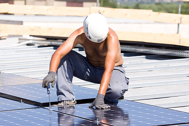 Man in a hard hat working on solar panels  stock photo