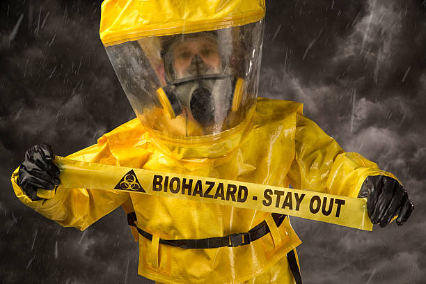Man in a hazmat Suit holding biohazard warning tape stock photo