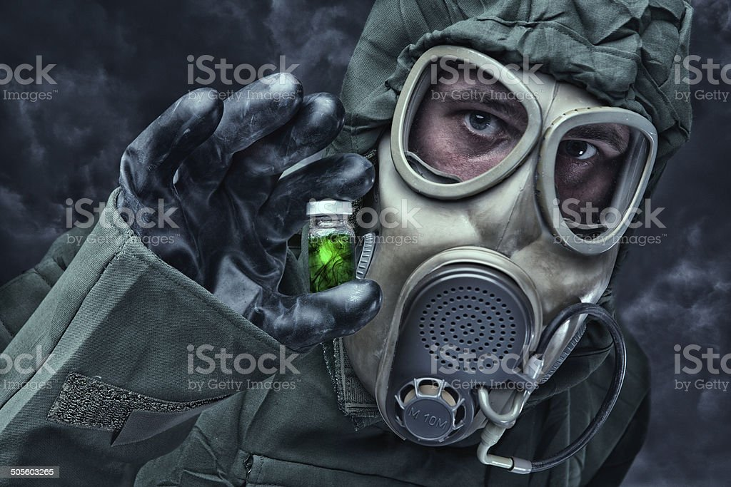 Man in a hazmat Suit holding vial stock photo