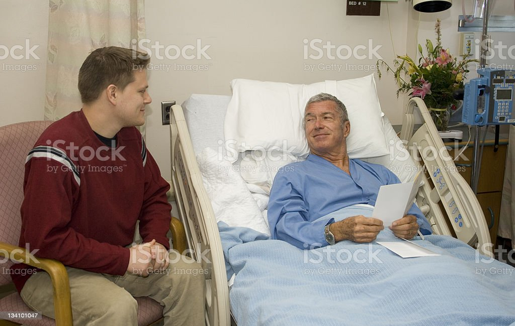 Man in a hospital bed smiles at visitor while reading card stock photo