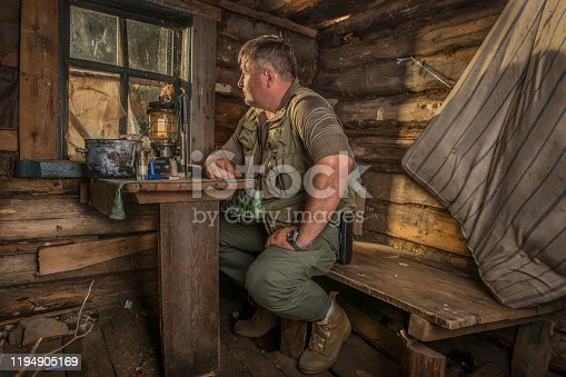 A man in a hunting Lodge at the table.