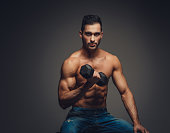 Shirtless muscular man in a jeans holding a dumbbell.