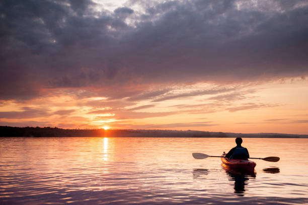 Man in a kayak on the river on the scenic sunset stock photo