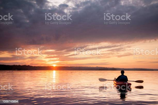 Photo of Man in a kayak on the river on the scenic sunset