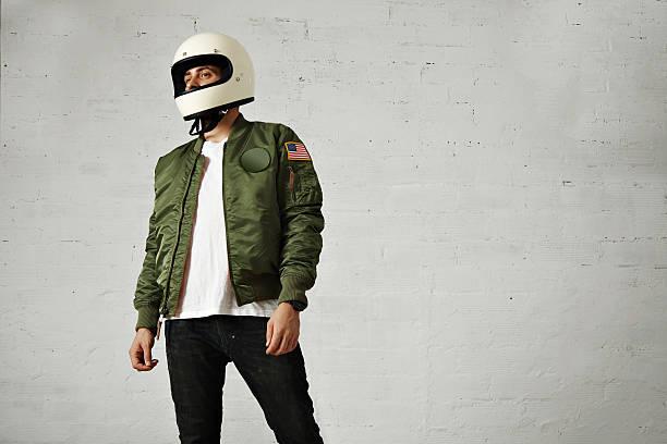 Man in a khaki pilot jacket with helmet stock photo