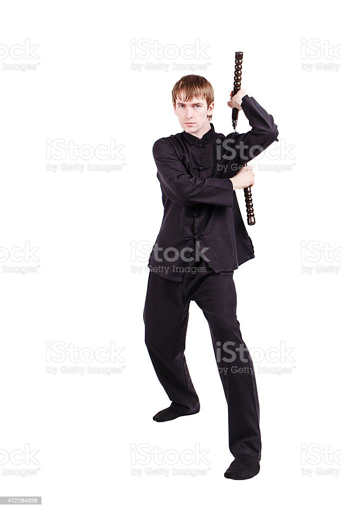 Man in a kimono practicing kung fu with nunchaku stock photo