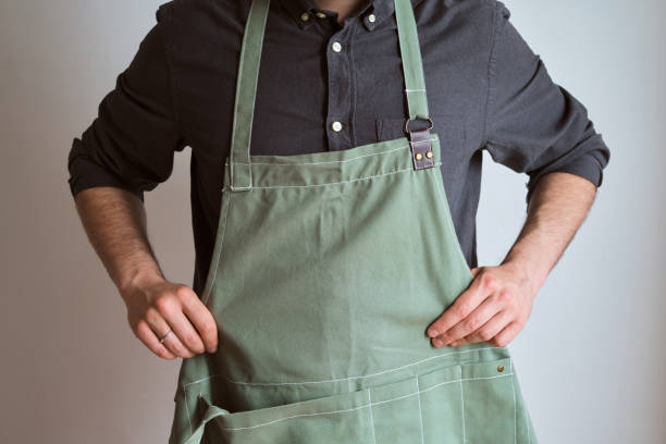 A man in a kitchen apron. Chef work in the cuisine. Cook in uniform, protection apparel. Job in food service. Professional culinary. Green fabric apron, casual stylish clothing. Handsome baker posing in workplace A man in a kitchen apron. Chef work in the cuisine. Cook in uniform, protection apparel. Job in food service. Professional culinary. Green fabric apron, casual stylish clothing. Handsome baker posing in workplace apron stock pictures, royalty-free photos & images