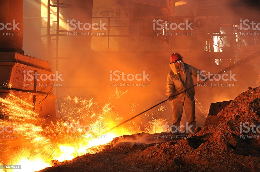 Man in a mask performing iron-making duties in a fiery pit stock photo