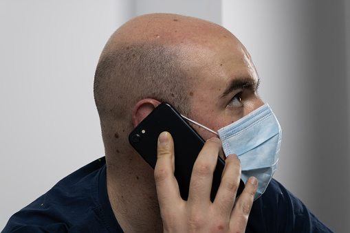 man in a mask talking on an isolated cell phone on a white background