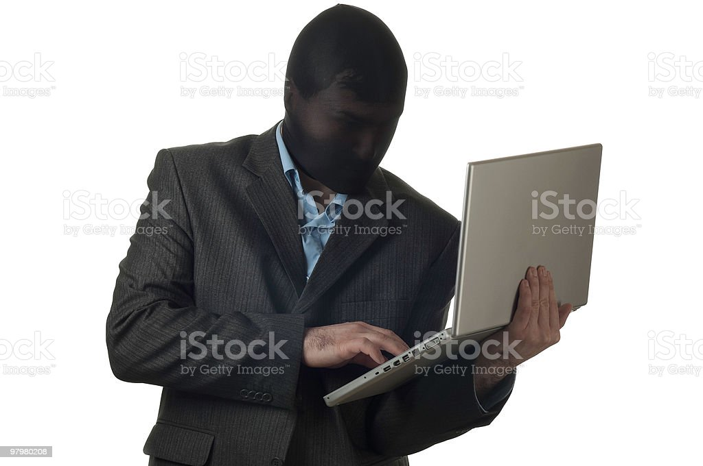 Man in a mask wearing suit holding laptop stock photo