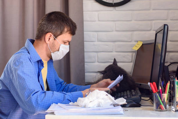 Man in a medical mask reads a document while working remotely picture id1214105194?b=1&k=6&m=1214105194&s=612x612&w=0&h=x 4k9s8bqex2vkf9ctbiy7v4c1h6tp gem6nizwa254=