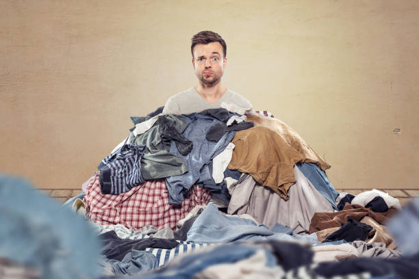 Man in a mess of laundry stock photo