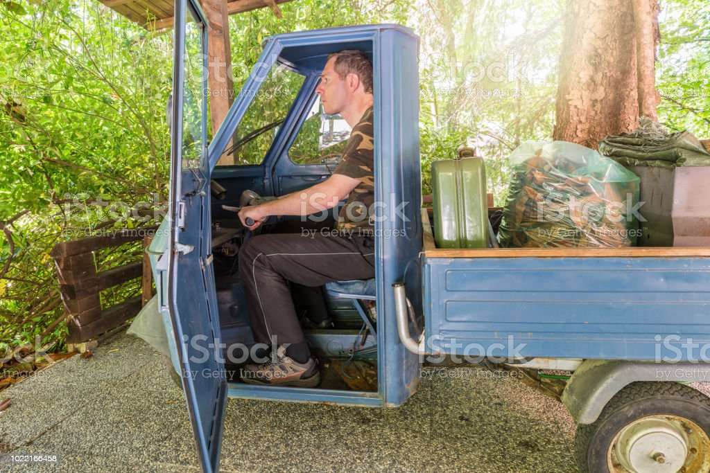 Man in a old three-wheeled single-seater vehicle, model produced between 1984 and 1985 used for gardening - foto stock