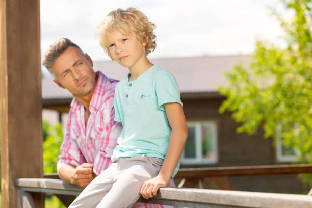 mann in einem rosa hemd genießen sonnigen tag mit seinem kleinen sohn - dorfkind momente stock-fotos und bilder