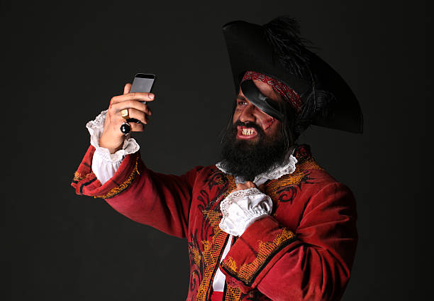 Man in a pirate costume with mobile phone, makes self Man in a pirate costume with hat and eye patch holding a mobile phone, makes self,  on black background  pirate criminal stock pictures, royalty-free photos & images