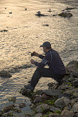 Istanbul, Turkey - November 22, 2020: Man in a protective face mask sitting on the rocks takes a photo or video of the seagulls with his smartphone. Relaxing on the seaside in quarantine days.