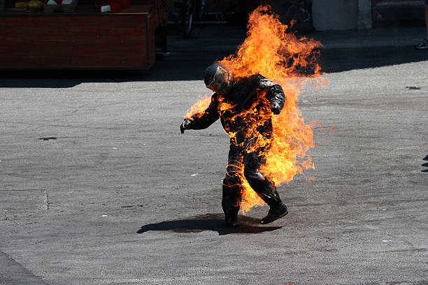 Man in a protective suit wrapped in flames stock photo